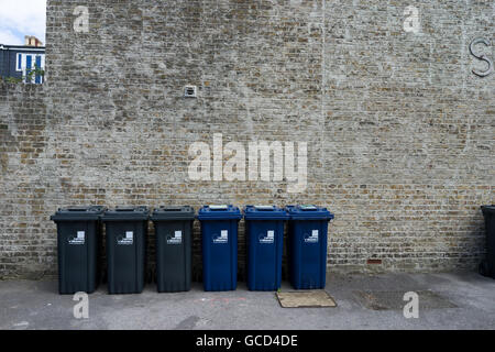 A row of wheelie bins against a brick wall, recycling - Stock Photo