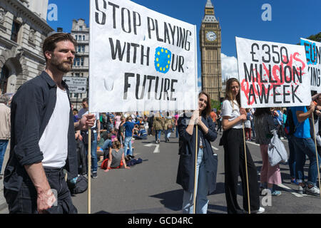 Anti-Brexit protestors wave banners against the UK Governments decision to leave European Union, crowds on street - Stock Photo
