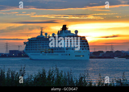 The World heads down the river Thames at sunrise after spending a few days moored at Greenwich, London.t - Stock Photo