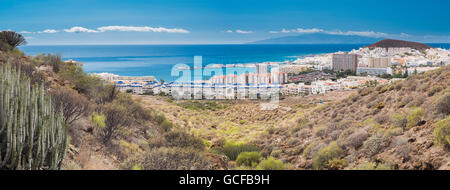 Panorama over the holiday resort of Los Cristianos, Tenerife, with the island of La Gomera in the background - Stock Photo