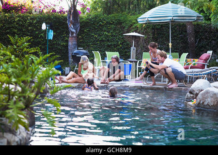 A family enjoys an afternoon in the pool on a sunny afternoon; Fountain Valley, California, United States of America - Stock Photo