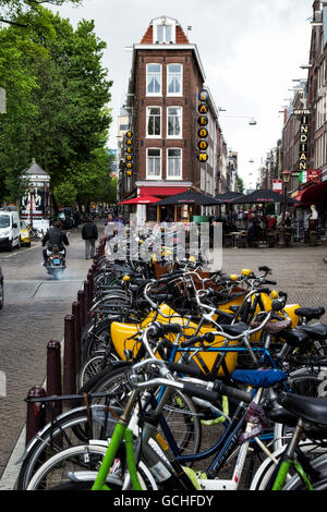 Numerous bicycles asked in a row along a street; Amsterdam, Netherlands - Stock Photo