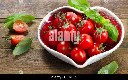 Fresh tomatoes in a heart shaped plate. Healthy eating. Top view - Stock Photo