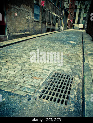 vintage toned image of old cobblestone alley in New York City - Stock Photo