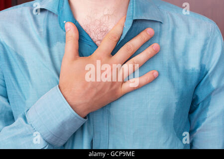 Sweaty spot on the shirt because of the heat, worries and diffidence - Stock Photo