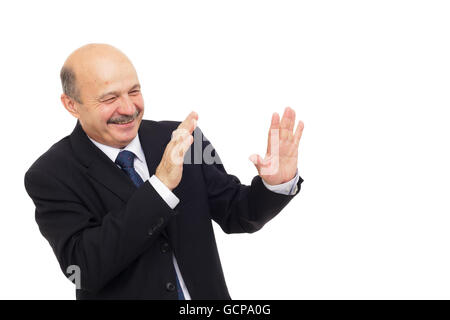 elderly man tries to protect himself with his hands, hiding from danger - Stock Photo