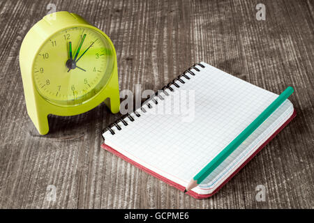 Time management concept: green alarm clock, pencil and notebook - Stock Photo