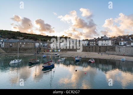 Mousehole harbour with clouds reflecting in the water - Stock Photo
