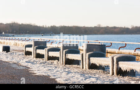 Benches near sea covered with thick ice layer in winter - Stock Photo