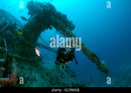 Female scuba diver at the anti-aircraft gun on wreck of the SS Thistlegorm (British armed Merchant Navy ship), Red - Stock Photo