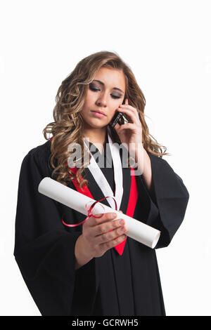 Young graduating woman holding her diploma and talking on her smart phone; Edmonton, Alberta, Canada - Stock Photo