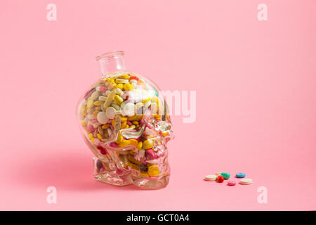 Creative medicine and health care concept photo of a skull glass filled with drugs and pills on pink background. - Stock Photo