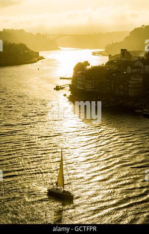 Douro river in the city of Porto at sunset with Ponte da Arrabida bridge in background. Portugal. - Stock Photo