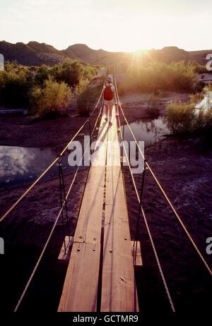 Female hiker crossing footbridge at sunset; southern Utah desert; USA - Stock Photo