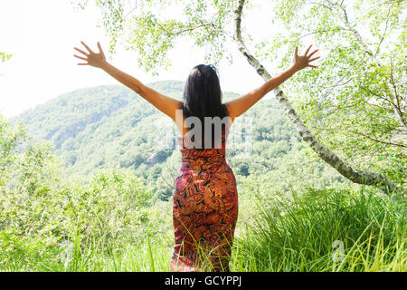 elegant woman with open arms in the forest - Stock Photo