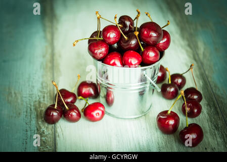 Cherries in a small metal bucket on a wood background - Stock Photo