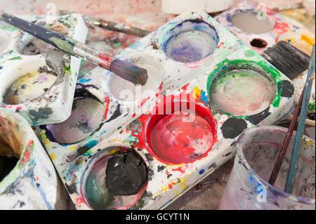 discarded left behind dirty paint brushes in butlers sink needing a serious clean and polish after messy art students - Stock Photo