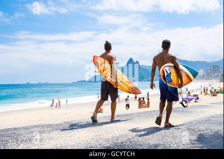 RIO DE JANEIRO - APRIL 3, 2016: Young carioca Brazilians walk with surfboards from Arpoador, the popular surf point. - Stock Photo