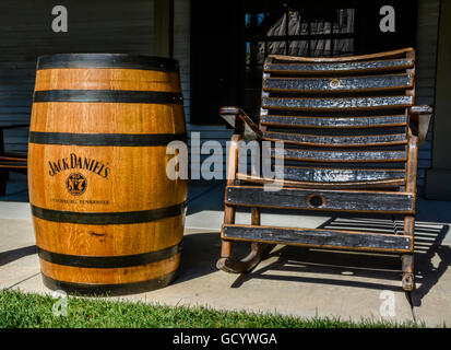 Black wooden lathe style rocking chair on porch along side an authentic oak Barrel of Jack Daniel's No 7 Whiskey, - Stock Photo