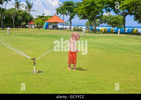 Happy baby boy play with sprinkler spray, swim and splash with fun under water drops on green grass lawn. - Stock Photo