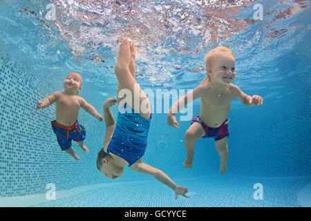 Funny photo of active babies swim and dive with fun - jump deep down underwater with splashes in swimming pool. - Stock Photo