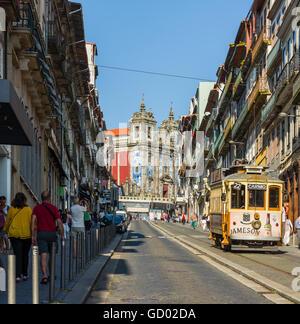 Tram crossing Rua 31 de Janeiro street with Igreja de Santo Ildefonso church in background. Porto. Portugal. - Stock Photo