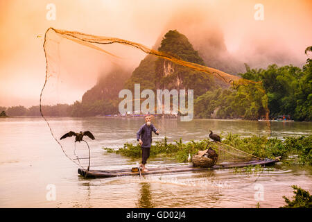 Traditional Chinese cormorant fisherman casts a net on the Li River in Yangshuo, China. - Stock Photo