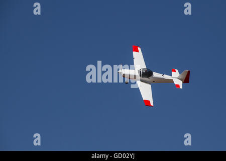 Top view of Small white airplane flying on clear blue sky - Stock Photo