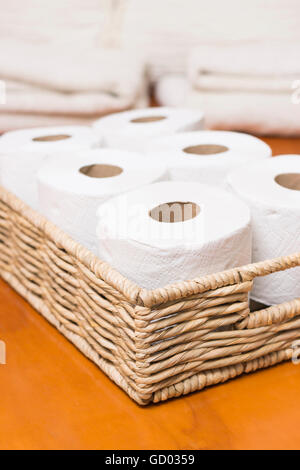 Toilet paper rolls on wicker basket - Stock Photo