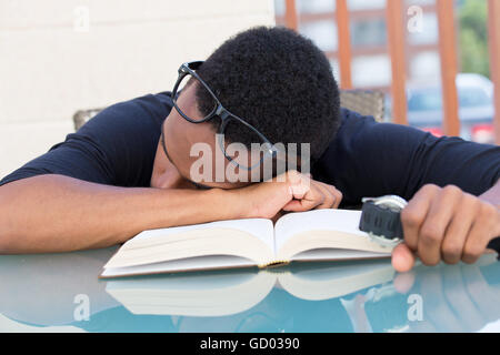 Closeup portrait, nerdy young man in big black glasses holding watch, falling very tired of reading, fast asleep, - Stock Photo