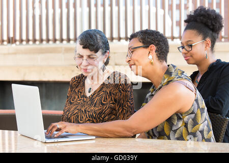 Closeup portrait, multigenerational family looking at something exciting on laptop, isolated outdoors background - Stock Photo