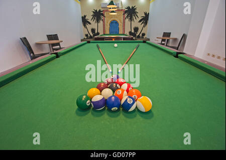 Closeup of billiard balls on green felt table with pool cues in games room - Stock Photo