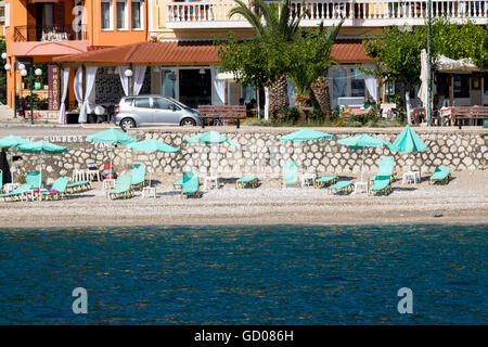 Detailed View of Poros Town Beach with Sun Loungers and Parasols, Promenade and Main Street, Kefalonia, Greece. - Stock Photo