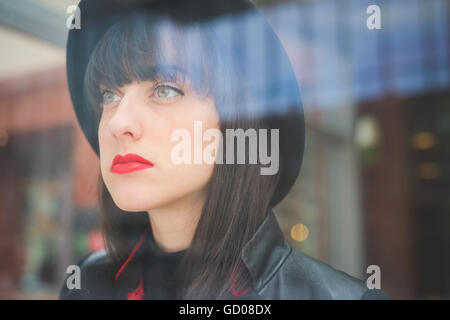 Portait of a young beautiful caucasian woman behind a showcase looking in camera- freshness, serene, carefree concept - Stock Photo