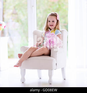 Little girl smelling peony flower bouquet sitting in a white chair in sunny bedroom. Nursery interior with flowers - Stock Photo