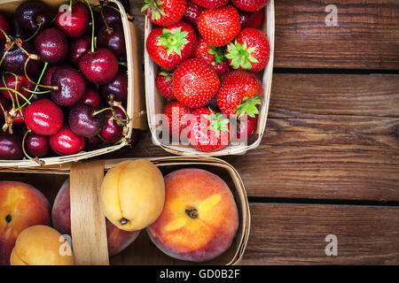 Fresh ripe summer berries and fruits (peaches, apricots, cherry, strawberry) in baskets, top view - Stock Photo