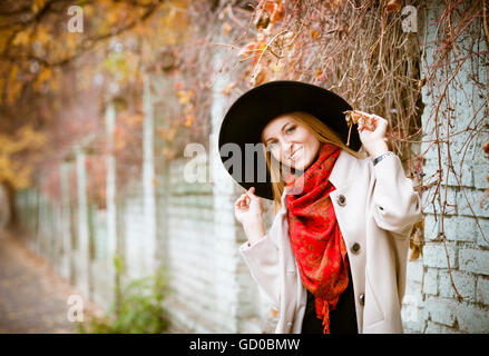 Beautiful young blond woman with long hair flying in the wind wearing hat in park - Stock Photo