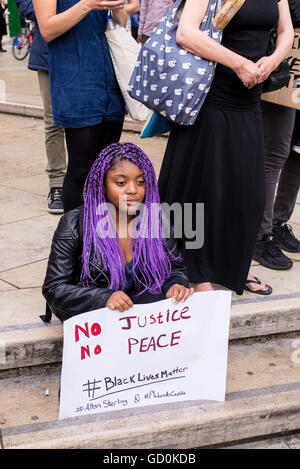 Brixton, London, UK. 9th July 2016. Young protester sitting in the street. Hundreds of Black Lives Matter Supporters - Stock Photo
