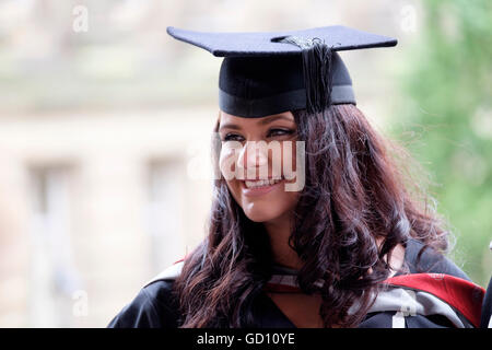 Happy, smiling attractive female student celebrating on graduation day - Stock Photo