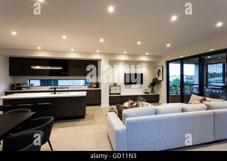 Modern Living Room With Chairs And Sofas Next To Tables Beside A Kitchen Windows That