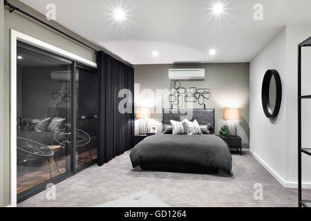 Black color bed in luxurious hotel or house  with flashing lamps beside a glass door or window - Stock Photo