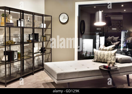 Small bed and pillows beside a shelf with fancy items like gold, statues, books and baskets in a luxury house. - Stock Photo