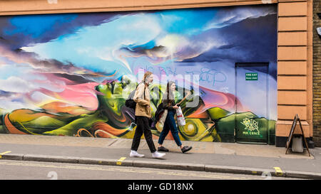 Hipster couple walking in front of a graffiti in a street in Soho, a trendy area in London famous for restaurants - Stock Photo