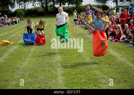Girls competing in sack race St James Primary School sports day Chipping Campden UK - Stock Photo