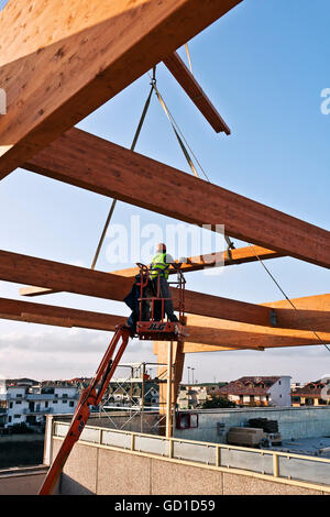Workman building a structural glulam frame on a cherry picker - Stock Photo