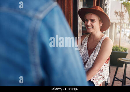 Smiling young woman sitting at a coffee shop with her friend. Young people sitting at a cafe table. - Stock Photo
