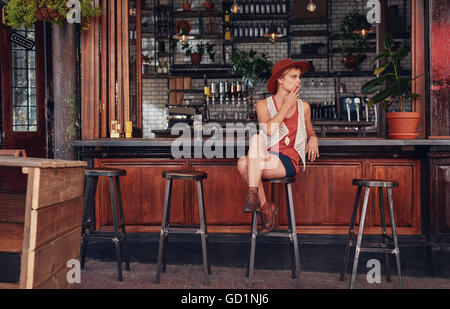 Young woman with hat smoking in a bar. Holding cigarette and looking away. - Stock Photo