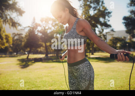 Outdoor shot of woman in sportswear exercising with skipping rope outdoors in a park. Fitness female working out - Stock Photo