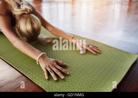 Female doing stretching workout on exercise mat. Woman doing balasana yoga at gym, with focus on hands. - Stock Photo