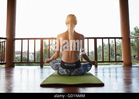 Rear view shot of young woman practicing yoga while sitting in lotus position on exercise mat. Sporty woman padmasana - Stock Photo